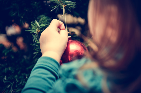 Little Girl is decorating Christmas Tree with home made Ornaments in retro filter effect Stock Photo - 48555948