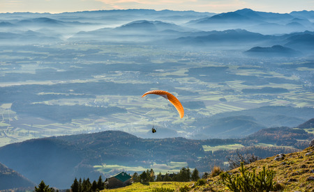high flier: Paraglider is flying in the valley. Paragliding from the mountain with perfect view