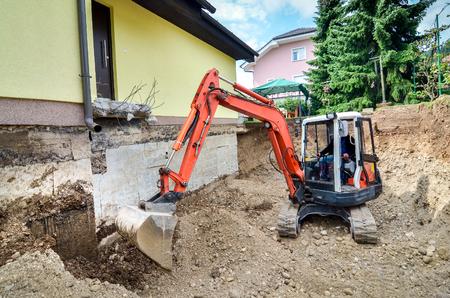 大きな家族の家は、掘削機の助けを借りて再構築中です。レンガと地下の水力発電の分離の具体的な基礎を掘り。 写真素材