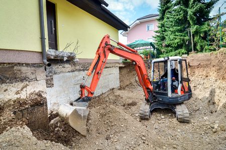 A big family house is being rebuilt with the help of an excavator. Digging the brick and concrete foundation for hydro isolation of basement. Stock Photo