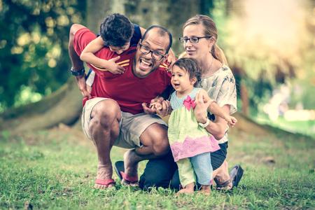 Gelukkig interraciale familie actief is en genieten van een dag in het park. Kleine mulat meisje en jongen. Succesvolle adoptie. Diverse familie in de natuur met de zon in de rug. Gezonde levensstijl.