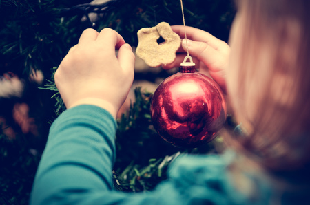 decorating christmas tree: Little Girl is decorating Christmas Tree with home made Ornaments