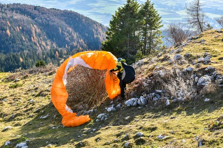 Paraglider accident. Parachute failed to start and got stuck in the bush. Saving the parachute after failure to start a paraglide. Reklamní fotografie - 48778615