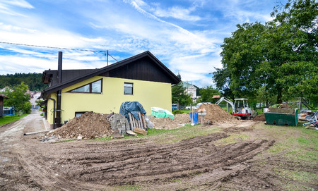 compacting: Rebuilding a family house and adding an  extension. Setting up a construction site with tools excavator and construction material.