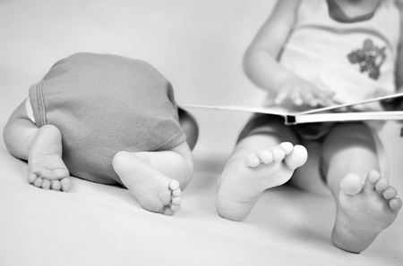 Little girl is reading a book tog her baby brother. Black and white photo with soft focus on their feet. Family values