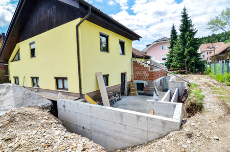 building foundation: Rebuilding a family house and adding an  extension. Setting up a construction site with formwork.. Stock Photo