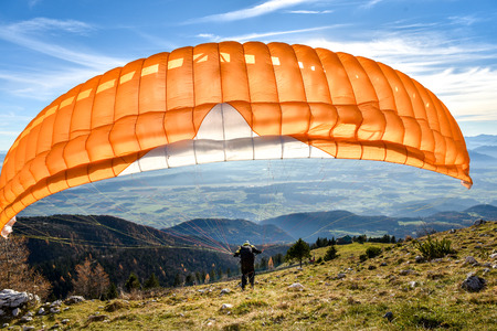 paragliding: Paraglider is starting. Parachute is filling with air in the mountains alps ona sunny day. Stock Photo