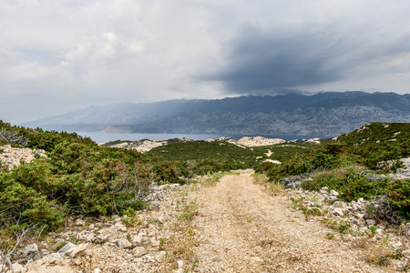 wind force: Storm is hitting coast of island Pag, making waves and splashes. Mountains Velebit in the background. Power and destructive force of wind. Adriatic sea - Croatia