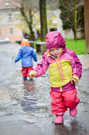 fun day: Twin babies in rain clothes are playing in the puddle. Rain coat protection from water - waterproof clothes.
