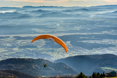 risk free: Paraglider is flying in the valley. Paragliding from the mountain with perfect view