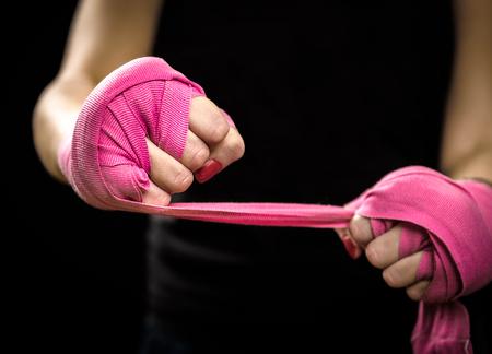 defensa personal: La mujer se está terminando la mano con envolturas de boxeo rosados. Aislado en negro con los clavos rojos. Mano fuerte y el puño, listo para la lucha y el ejercicio activo Foto de archivo