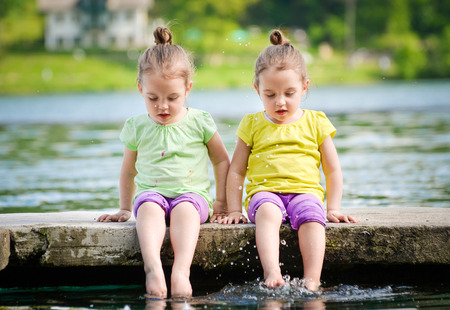Twin girls are exercising on a lake shore, sprinkling water.