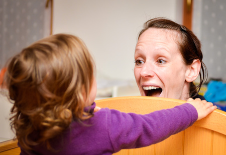 peekaboo: Mother and child are playing peekaboo or peek-a-boo on a children bed and having fun. Stock Photo