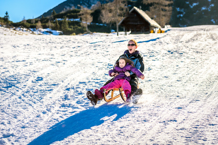 braking: Mother and little child are sledging very fast in ski mountain resort. High speed braking. Active family vacation on snow in the nature. Stock Photo