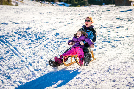 Mother and little child are sledging very fast in ski mountain resort. High speed braking. Active family vacation on snow in the nature. Stock Photo