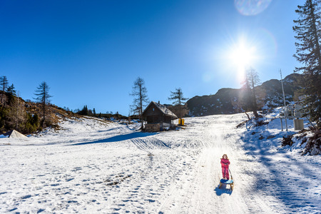 sledging people: Girl is pulling snow sledge in ski resort  wearing winter clothes. High mountain ski resort, vacation, holiday and sunny day mountain peaks.