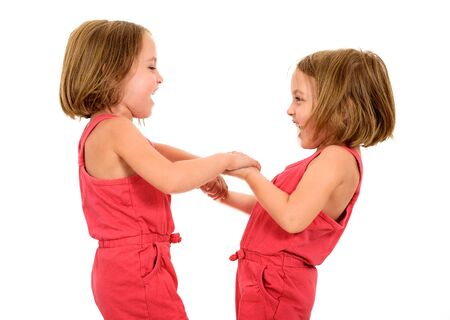 Portrait of Little Twin Girls celebrating and holding hands. Happy joyful children are enjoying achievement laughing in celebration. Active youth. Stock Photo
