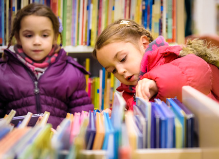 education book: Little girl is choosing a book in the library. A child is looking at the books in the library deciding which one to take home. Children creativity and imagination.