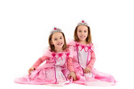 작은 쌍둥이 여자의 초상화 분홍색으로 공주처럼 옷을 입고. 행복 한 아이 의상 파티를 준비합니다. 귀여운 미소 즐거운 쌍둥이 공주 또는 왕비의 로열