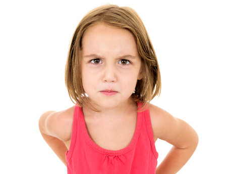 one child: Little girl is angry, mad and looking at the camera. Emotion face.