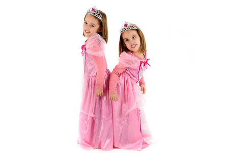 Portrait of Little Twin Girls dressed as princess in pink. Happy children ready for costume party. Cute smiling joyful twins are wearing royalty costume of princess or queen.