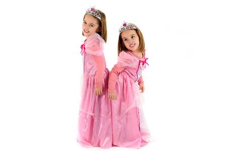 princesa: Retrato de Pequeños chicas gemelos vestido como princesa en color rosa. Felices los niños listos para la fiesta de disfraces. sonriendo gemelos alegres lindos están usando traje de derechos de princesa o reina.