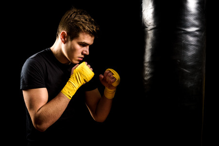 aerobic training: Attractive young man in yellow boxing wraps is training and hitting heavy bag. Fitness, aerobic exercise for active people. Strong athlete isolated on black. Stock Photo