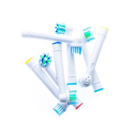 Different Electric Toothbrush replacement heads with color rings, isolated on white background.