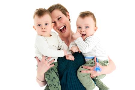 母は双子の男の子を運ぶと笑顔します。双子と母の幸せな家族。 写真素材