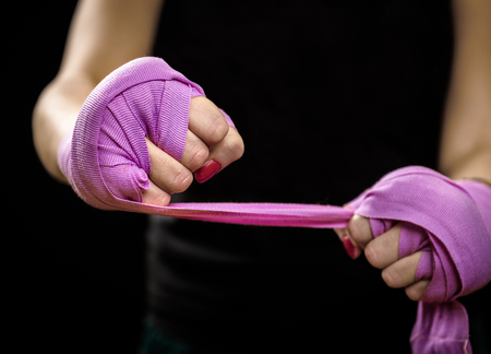 girl punch: Woman is wrapping hands with green boxing wraps. Isolated on black with red nails. Strong hand and fist, ready for fight and active exercise. Women self defense. Stock Photo