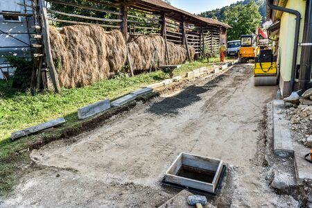 making earth: Making and constructing a new asphalt road with sewer pipes, truck and excavator or dredger earth mover and a roller. The sand stage of construction process.