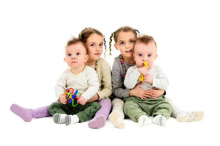 Having twins twice. Two pairs, sets of twin baby and twin children. Identical twin sisters are hugging identical twin brothers. Stock Photo