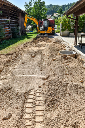 making earth: Making and constructing a new asphalt road with sewer pipes, truck and excavator or dredger earth mover. The sand stage of construction process. Stock Photo