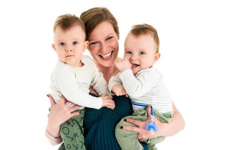 母は双子の男の子を運ぶと笑顔します。双子と母の幸せな家族。 写真素材 - 54969996