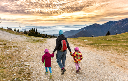 foot path: Family hiking in the mountains on ski slope into sunset. Mother and two twin children are hiking on the foot path in the nature in alps and hills. Active family . Stock Photo