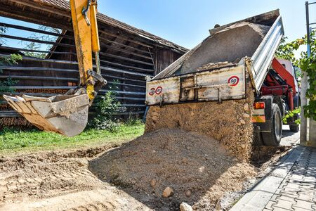 purring: Making and constructing a new asphalt road with a truck purring the sand. The sand stage of construction process. Stock Photo