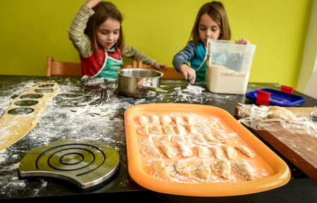 ni�as gemelas: Family with twin girls is making home made pastry dumplings tortellini or ravioli. Foto de archivo