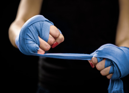 Woman is wrapping hands with blue boxing wraps. Self Defense for Women. Isolated on black with red nails. Strong hand and fist, ready for fight and active exercise Standard-Bild