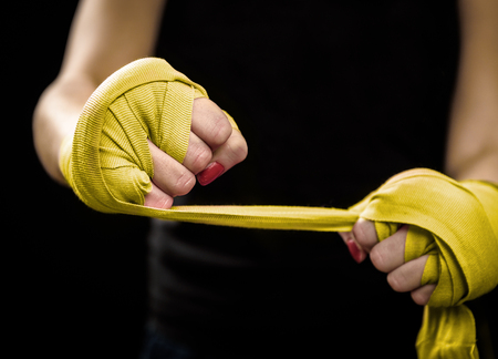 wraps: La mujer se está terminando la mano con envolturas de boxeo amarillos. Defensa Personal para Mujeres. Aislado en negro con los clavos rojos. Mano fuerte y el puño, listo para la lucha y el ejercicio activo Foto de archivo