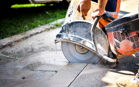 Construction worker cutting Asphalt paving stabs for sidewalk using a cut-off saw. Profile on the blade of an asphalt or concrete cutter with workers shoes and protective gear.