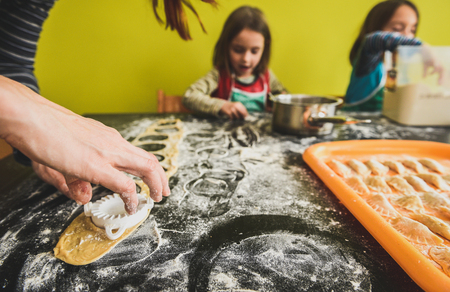 niñas gemelas: Familia de gemelas está haciendo albóndigas caseras tortellini pastelería o los raviolis.