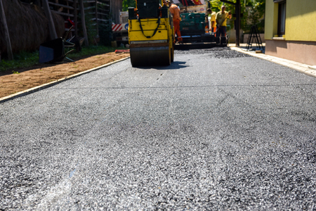 Team of Workers making and constructing asphalt road construction with steamroller and the finisher. The top layer of asphalt road on a private residence house driveway