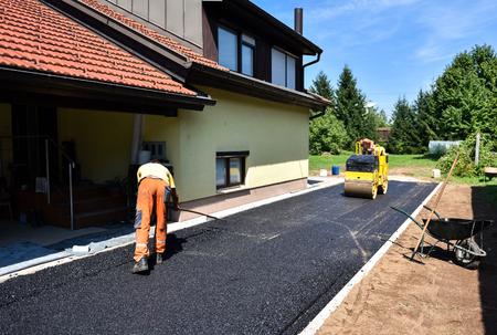 Equipo de trabajadores de la construcción de decisiones y la construcción de carreteras de asfalto con la apisonadora. La capa superior de la carretera de asfalto sobre una calzada casa residencia privada