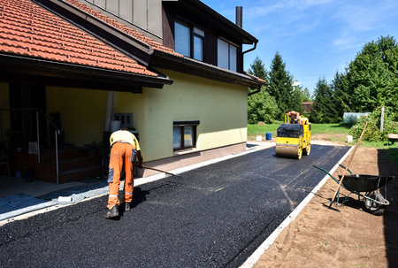 Team of Workers making and constructing asphalt road construction with steamroller. The top layer of asphalt road on a private residence house driveway Imagens - 54970832