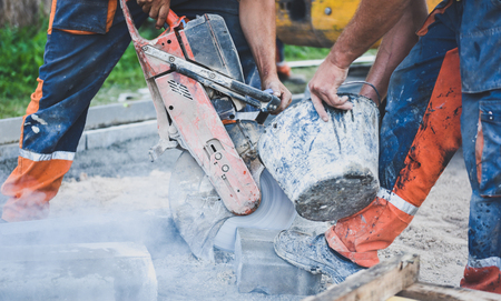 stabs: Construction worker cutting concrete paving stabs or metal for sidewalk using a cut-off saw. Profile on the blade of an asphalt or concrete cutter with workers shoes and protective gear.