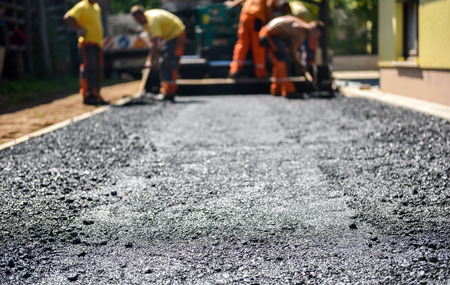 Team of Workers making and constructing asphalt road construction with finisher. The top layer of asphalt road on a private residence house driveway Standard-Bild