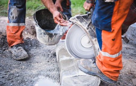 cut off saw: Construction worker cutting concrete paving stabs or metal for sidewalk using a cut-off saw. Profile on the blade of an asphalt or concrete cutter with workers shoes and protective gear.