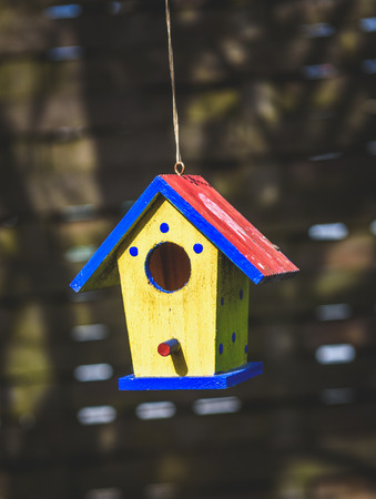 small roof: An old weathered DIY birdhouse hanging from the tree. Colorful small bird house with red roof, yellow walls and blue spots. Stock Photo