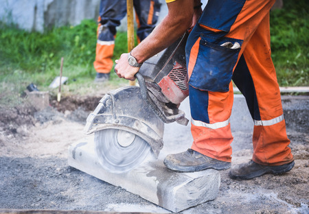 Construction worker cutting concrete paving stabs or metal for sidewalk using a cut-off saw.