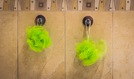 bathroom tiles: Two green bath sponges hanging from the bathroom wall. Bath accessories hanging from bathroom tiles.